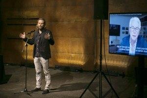 Pressemøde. Til venstre ses instruktøren og på skærmen ses forfatteren. Foto: Mikkel Østergaard